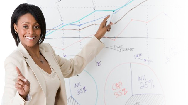 Woman smiling whilst pointing to graphs on a whiteboard